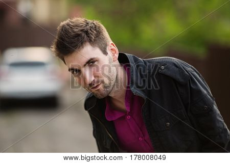 Casual wear. Young attractive cheerful casual man with dark hair with a beard wearing a shirt and a black jacket on the street. Male street style. Nature in spring. Casual man Walking around the city. Casual guy