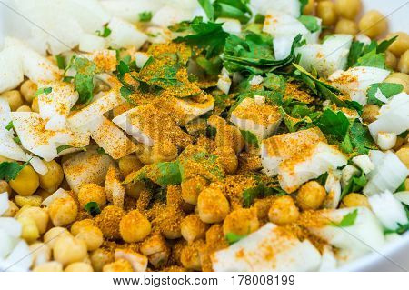 Cheakpeas with garam masala spices, onions and leaves of parsley. Close-up image of cooked chickpeas, chopped onion, garlic and fresh parsley in bowl seasoned with indian curry spices