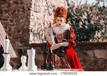 The Red Queen is playing chess. Red-haired woman in a chic vintage dress. Fashion Photo. Win a victory. Victory in the battle. Victory in game in chess