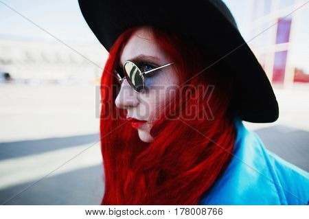Woman with red curly hair in blue coat and black round glasses and hat on background of big city. Red-haired girl with pale skin and bright appearance with black hat on head. Street style. Black hat