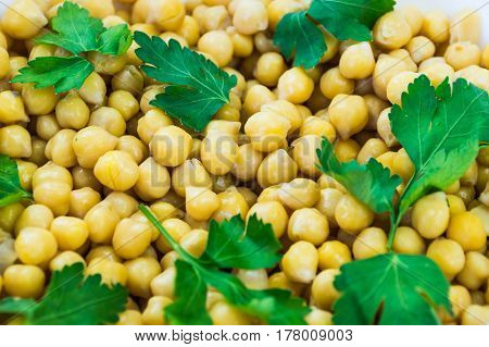 Cheakpeas and leaves of parsley. Close-up image of cooked chickpeas and fresh parsley in bowl