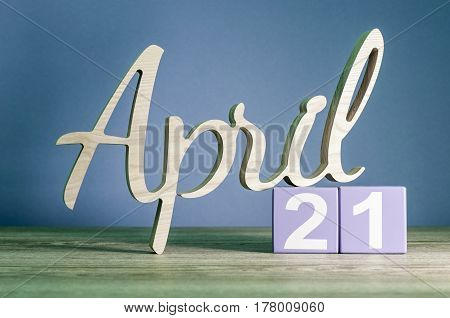 April 21st. Day 21 of month, daily calendar on wooden table with purple or violet background. Spring time theme.