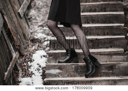 Women's shoes street style. Winter Autumn black women's shoes. Shoes on feet. To climb up the stairs. Autumn shoes