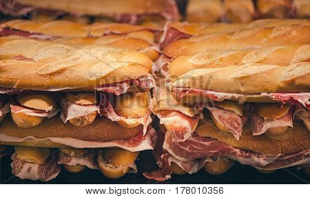 French loaf with Spanish jamon. Spanish Iberico Jamon. Traditional Spanish Ham. Thin slices of the Iberico jamon between two pieces of bread