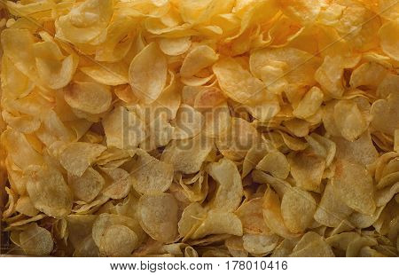 A lot of potatoes chips. Yellow salted potato chips as background. Chips texture.
