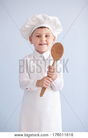 Child in cap cook. child cook baby with a spoon
