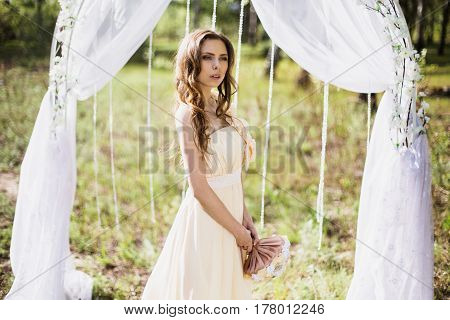Beautiful wedding aisle. Beauty portrait of a very pretty young girl. Doll appearance. Woman with brown hair in a pink wedding dress on nature near the wedding aisle. Long hair. Natural light. Model posing in nature. Wedding aisle