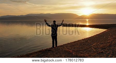 Magnificent scenery of sunset over lake prespa in macedonia, man celebrate sun