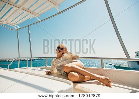 beautiful blonde sunbathing on a yacht on sea