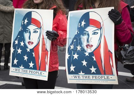 45th Presidential Inauguration, Donald Trump: We The People with a picture of a woman wearing a head scarf on a sign held by a protestor outside the security checkpoint, WASHINGTON DC - JAN 20 2017