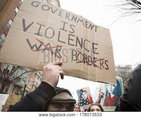 45th Presidential Inauguration, Donald Trump: Government Is Violence on a sign held by a protestor outside the security checkpoint, WASHINGTON DC - JAN 20 2017