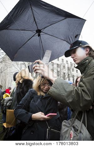 45th Presidential Inauguration, Donald Trump: People waiting at a security checkpoint watch the inauguration on the cellphones in the rain, WASHINGTON DC - JAN 20 2017