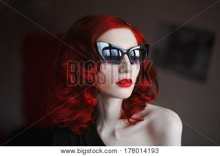 Noir woman with her red curly hair in a black dress and fox glasses on a dark background. Red-haired noir girl with pale skin blue eyes a bright unusual appearance with red lips looking out the window. Noir model
