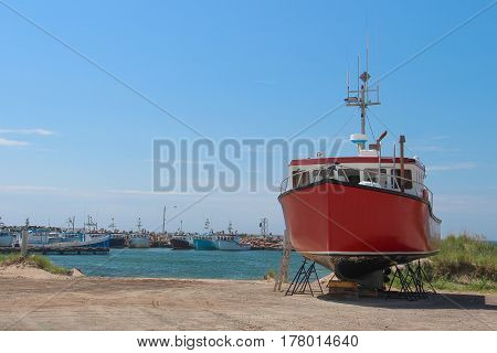 Red fishing boat in dry dock in Magdalen Island with port and other boats in the background uner a blue sky