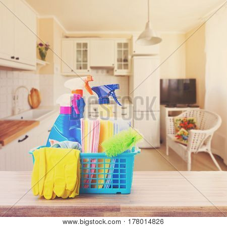 Spring cleaning concept - colorful spays and rubbers on table in kitchen, retro toned