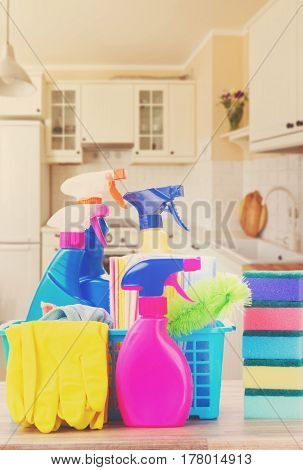 Spring cleaning concept - colorful spays and rubbers on wooden table in kitchen, retro toned