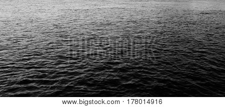 Water with waves by day may be used as background. Black and white.