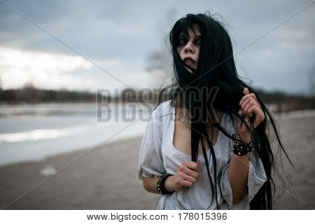 Portrait Of Crazy Young Woman With Disheveled Hair Near Lake.