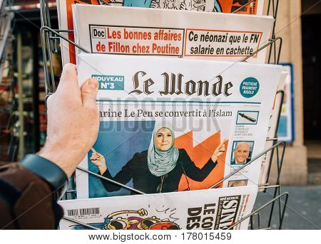 PARIS FRANCE - MAR 23 2017: Le Wonde satiric journal with title Marine le Pen - Conversion to Islam newspaper from press kiosk newsstand featuring headlines