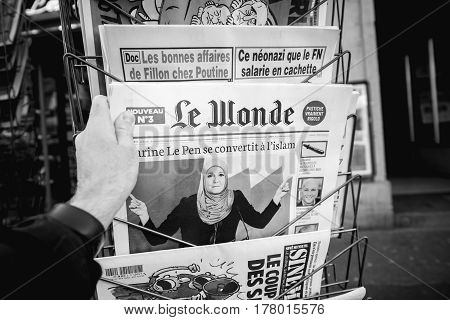 PARIS FRANCE - MAR 23 2017: Le Wonde satiric journal with title Marine le Pen - Conversion to Islam newspaper from press kiosk newsstand featuring headlines - black and white image