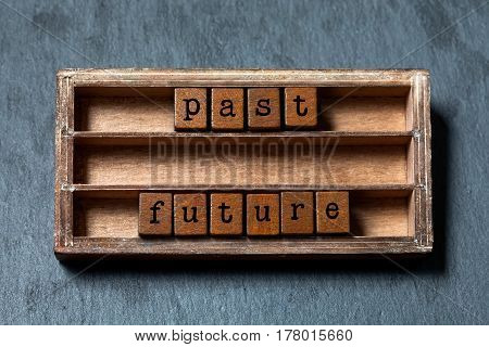 Past future concept. Vintage box, wooden cubes phrase with old style letters. Gray stone textured background. Close-up, up view, soft focus