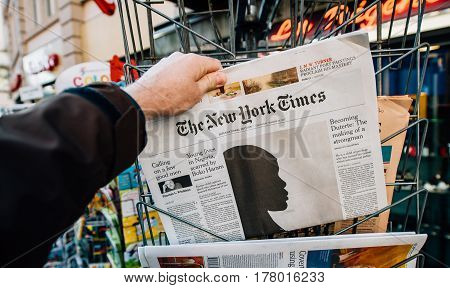 PARIS FRANCE - MAR 23 2017: Man purchases The New Yprk Times with Boko Haram article on cover page - newspaper from press kiosk newsstand featuring headlines