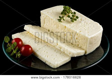 Slices of traditional sfella cheese of Peloponnese, Greece, on plate with little tomatoes and oregano
