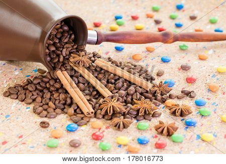 A tumbled clay jezva jar filled with coffee beans anise and cinnamon sticks with colorful candies