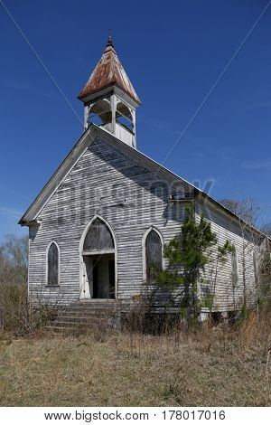 old abandoned church with rusted tin roof and peeling white paint