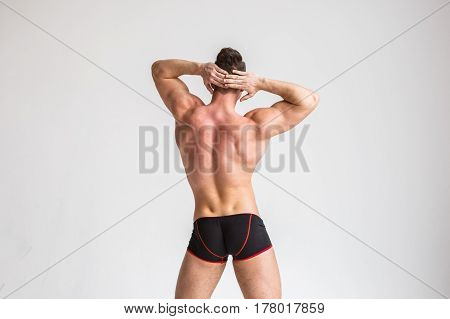 Beautiful sexy muscular naked man posing in his underwear on a white background