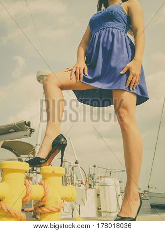 Dominant feminist woman wearing high heels and short blue dress standing one leg on big industrial bolt in marina.