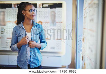 Grinning Woman Next To Eyeglasses Display