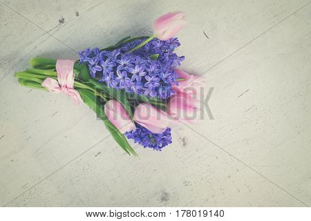 Pink tulips and blue hyacinths flowers bouquet on white wooden table, retro toned