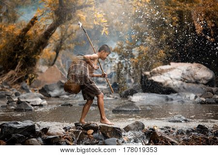 Asian boy fishing in creeks Children fight life