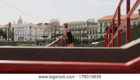 Tourism in Panama City. Young blonde Colombian woman leaning on red rails visiting Casco Antiguo and looking at panorama.