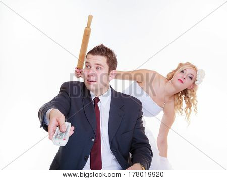 Relationship problems and troubles concept. Groom and bride having quarrel argument woman holding rolling pin man wants to watch tv