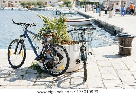 Two bicycles parked in flowerbeds in a European city near the sea summer and sunny weather beautiful light