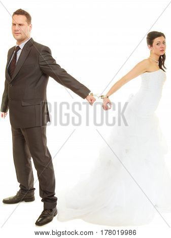 Couple problems love forever concept. Bride and groom in handcuffs wearing wedding outfits
