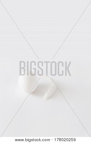 Easter decoration minimalistic white egg and a white chicken feather lying on a white background daylight vertical image