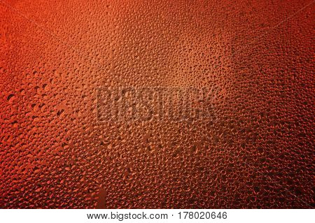 Extreme close-up of morning dew on glass with reddish background