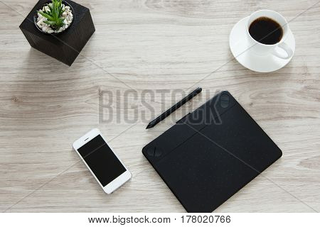 Workplace. On the wooden table there is a graphics tablet stylus mobile phone pot with flowerpots and white cup of coffee.