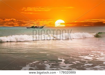 Beautiful sunrise tropical beach white sand turquoise ocean water . Boats of fishermen on the water.