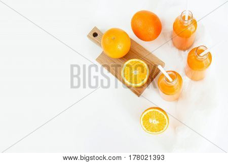 Three bottles of orange juice and tubes are on the table on a white background as much as two oranges and one orange cut into wooden Boards. Daylight horizontal image.