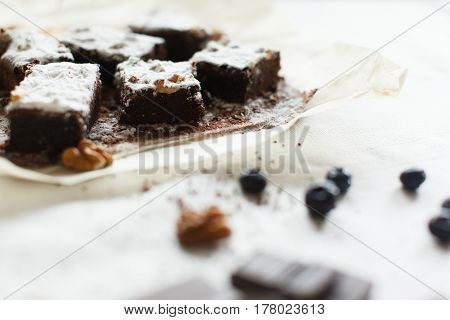 Table setting chocolate dessert brownie cake with berries on parchment paper on a table covered with a linen tablecloth. Horizontal shot daylight.