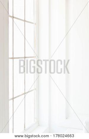 Light minimalist laconic interior with white walls large windows. Daylight vertical shot.