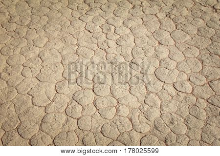 Clay texture of drying prism desiccation cracks in ground. Cracked and dried mud dirt background texture in the desert.