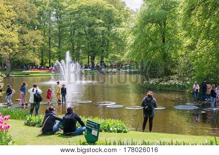 KEUKENHOF THE NETHERLANDS - MAY 10 2015: People chilling out in the sun in Keukenhof park in Netherlands Europe. Visitors are having a rest.