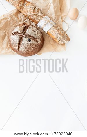 Cooking of homemade bread black round bread and baguette lie on parchment paper on a white background with eggs. Space for text daylight.