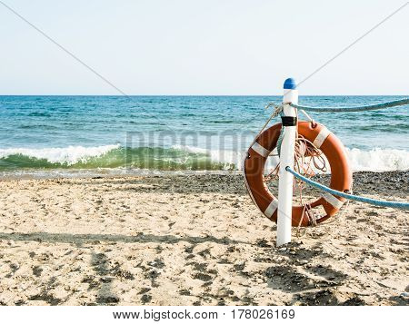 Lifebuoy on a sandy sea beach in Terracina Italy. Safe swimming in the sea and ocean. Background for a marine theme or safety during vacation