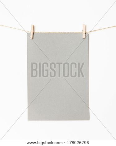 Gray sheet for applying text is attached by wooden clothespins on a white background. Write your text.